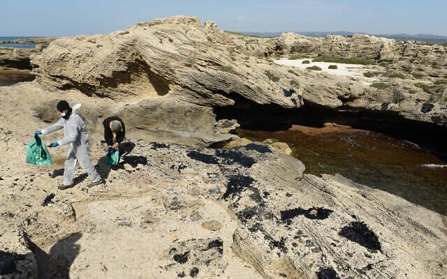 Israelis clean tar from the sand after an offshore oil spill drenched much of Israel's Mediterranean shoreline, at a beach in Atlit, Israel February 22, 2021. Photo by: Roni Ofer-JINIPIX