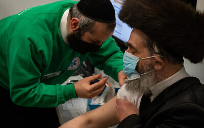 Strictly-Orthodox man receives his jab from a Jewish volunteer