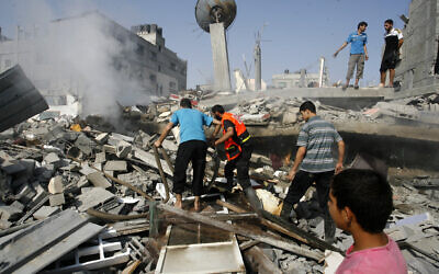 Palestinians extinguish a fire in a collapsed building, hit during an Israeli strike in the southern Gaza Strip in 2014.   Photo by Abed Rahim Khatib/Pacific Press/ABACAPRESS.COM