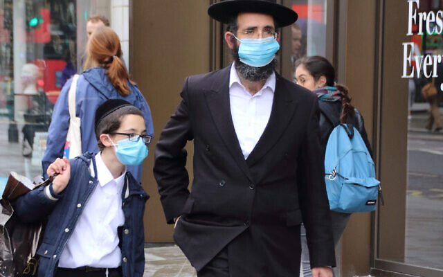 A Jewish man with his son walk along Oxford Street while while wearing face masks as a preventive measure against the spread of Coronavirus.