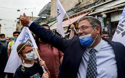 Itamar Ben Gvir (R), head of Israel's Jewish Power (Otzma Yehudit) party, cheers to supporters at the Mahane Yehuda market in Jerusalem, on March 22, 2021 while campaigning a day ahead of the fourth national election. (Photo by MENAHEM KAHANA / AFP) (Photo by MENAHEM KAHANA/AFP via Getty Images)
