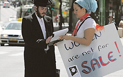 A man signs a petition at a demonstration for women's rights held outside the Rabbinical court for divorces.