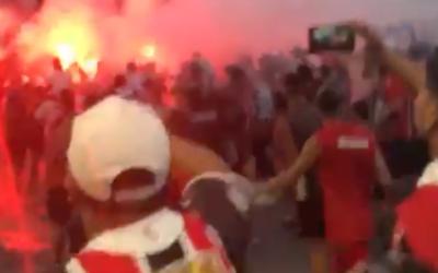A screenshot from the viral video of Chacarita fans chanting an anti-Semitic line shows them marching near a bonfire on the street. (Screenshot via JTA)