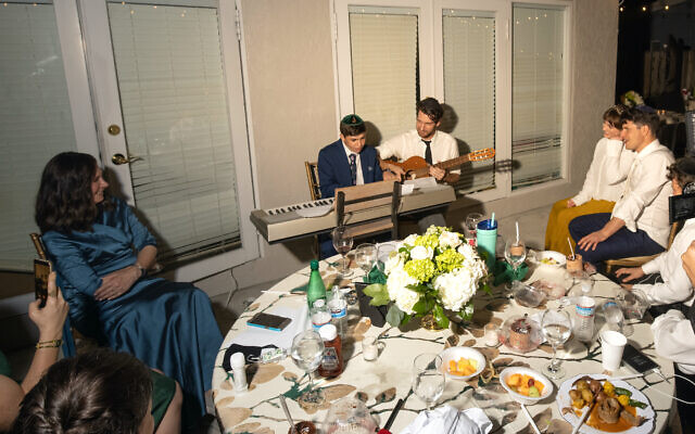 """Judy Kaiser (left) and her son Menachem Kaiser (holding the guitar next to his nephew) pictured together at his brother's wedding. Author Menachem has received date offers after his mother announced """"he's single"""" to an online conference with a synagogue about his new book."""