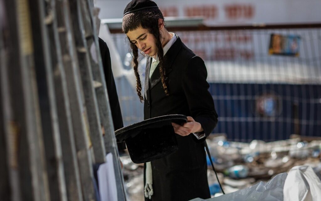 An strictly-Orthodox youth inspects leftover personal items at Mount Meron after the stampede (Photo:Ilia Yefimovich/dpa/Alamy Live News)