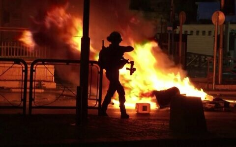 An Israeli officer stands in front of a fire burning in the street in Jerusalem on Thursday night (Photo: Reuters)