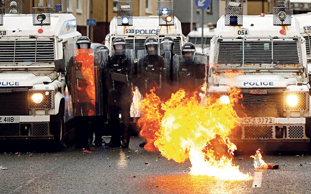 A fire burns in front of the police on the Springfield Road as protests continue in Belfast, Northern Ireland April 8, 2021. REUTERS/Jason Cairnduff