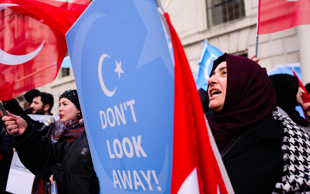 A woman seen shouting slogans while holding a placard during a protest against the Chinese policies in Xinjiang.
