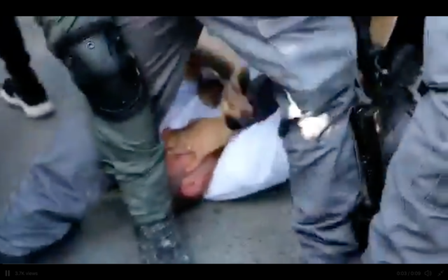Ofer Cassif being held by police. (Screenshot from Twitter)