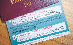 Vaccine certificate issued by NHS UK with second Astra Zeneca vaccination stamped, certificate tucked inside UK passport. Credit: Malcolm Park/Alamy Live News.
