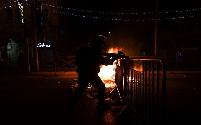 An Israeli policeman next to a burning barricade during clashes with Palestinians on Saturday night in Jerusalem's Old City, May 8, 2021. (Photo: Reuters/Ronen Zvulun)