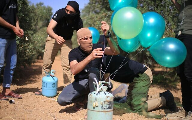 Masked young Palestinians, filled balloons with Helium Gas then they connect it with flammable object before they transport the balloons towards Israel. Credit: Mahmoud Khattab/Quds Net News/ZUMA Wire/Alamy Live News