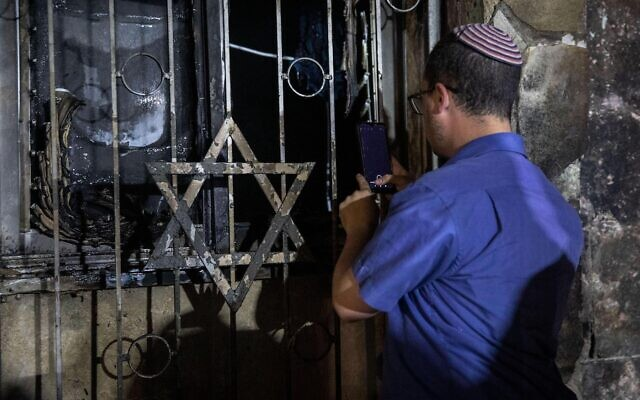 An Israeli man looks into a synagogue after it was set on fire during clashes between Jews and Arabs amid violent unrest in the mixed Israeli-Arab city of Lod. Credit: Oren Ziv/dpa/Alamy Live News