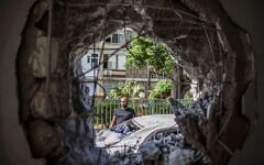 A man stands near a destroyed car and inspects a hole on a wall at a house that was hit by a rocket fired from the Gaza Strip towards Israel amid the escalating flare-up of Israeli-Palestinian violence. Credit: Ilia Yefimovich/dpa/Alamy Live News