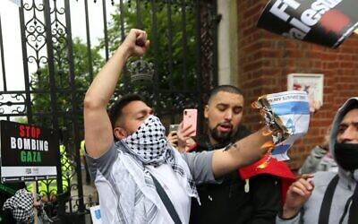 A protester burns the Israeli flag.