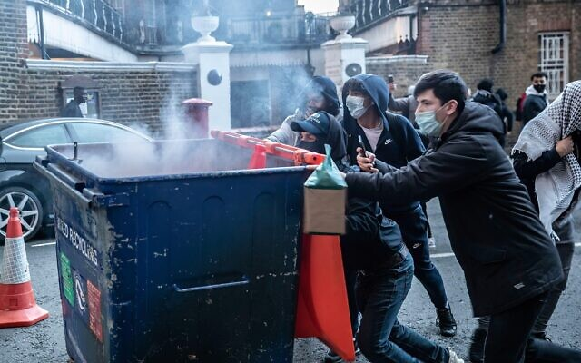 Rioters push a recycling bin towards police during the demonstration.