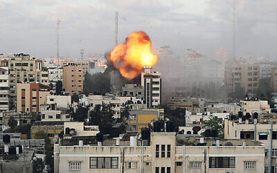 Smoke and flames are seen following an Israeli air strike on a building, amid a flare-up of Israeli-Palestinian fighting, in Gaza City May 18, 2021. REUTERS/Mohammed Salem