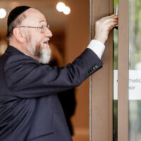 Chief Rabbi Mirvis affixing the Mezuza at the new home