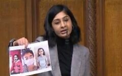 Zarah Sultana holding up pictures of three children killed in Gaza