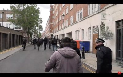 Screenshot shows police officer with a demonstrator as antisemitic chants are made