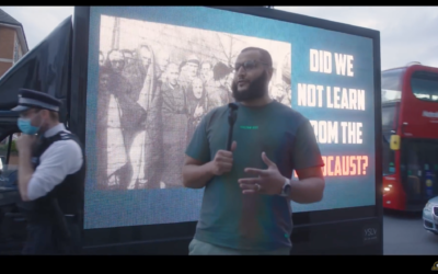 Mohammed Hijab in front of an electronic banner asking if we have 'learned from the Holocaust'