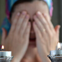 Jewish woman says the blessing upon lighting the sabbath candles before shabbat eve dinner.