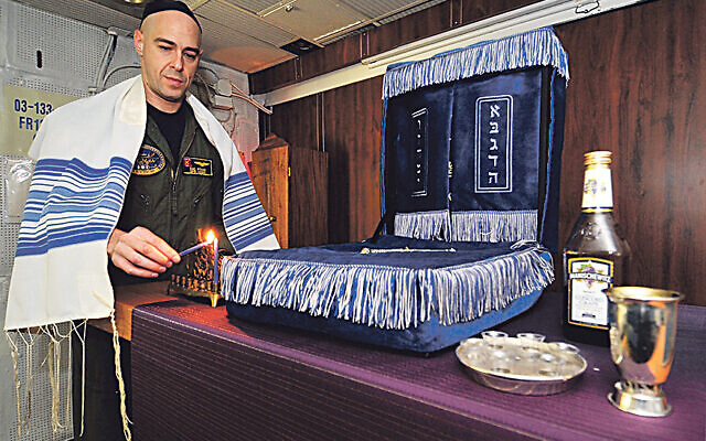 Jewish lay leader of the Nimitz-class aircraft carrier USS Harry S. Truman (CVN 75), lights a candle celebrating the 1st night of Hanukah in the ship's chapel.   (U.S. Navy photo by Mass Communication Specialist 2nd Class Kilho Park/Released)