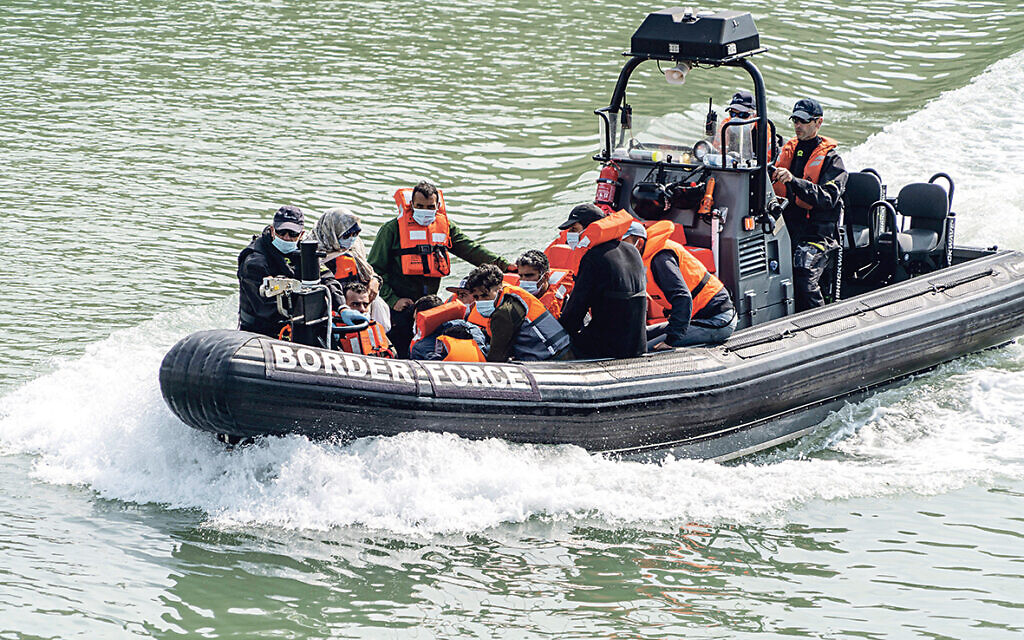 Migrants wearing face masks and life jackets being brought on shore by the border force at Dover