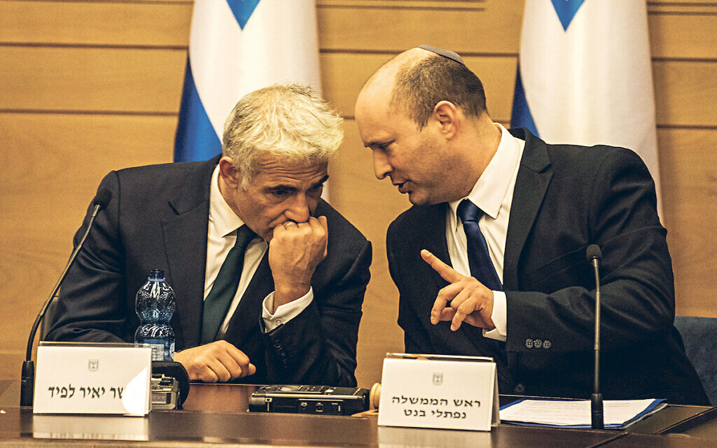 New Israeli Prime Ministers Naftali Bennett (R), leader of the Yamina right-wing alliance, and Yair Lapid, leader of the Yesh Atid opposition centrist party attend first cabinet meeting at the Israeli Parliament (Knesset).