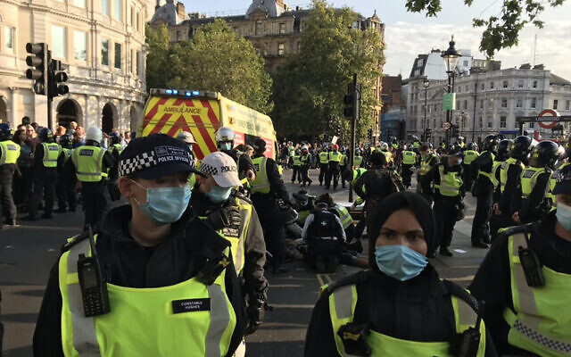 Picture taken with permission from the twitter feed of @bollin_anne of police officers tending to person injured during an anti-vax protest in London's Trafalgar Square.