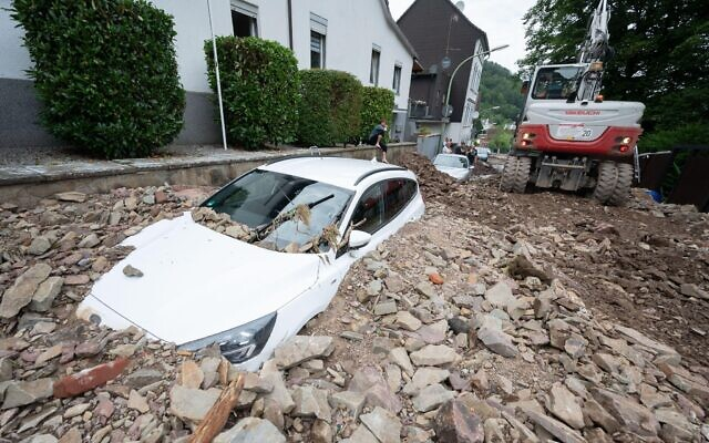 A car is buried by rubble in the Hohenlimburg district of Hagen, western Germany. (Photo: Julian Stratenschulte/dpa)