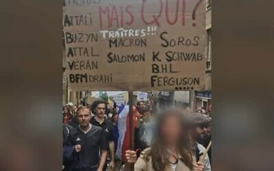 A woman holds up a placard denouncing President Emmanuel Macron and several prominent Jews denounced as traitors at a protest against COVID restrictions in Metz, France on Aug. 7, 2021. (Gérald Darmanin/Twitter) via JTA