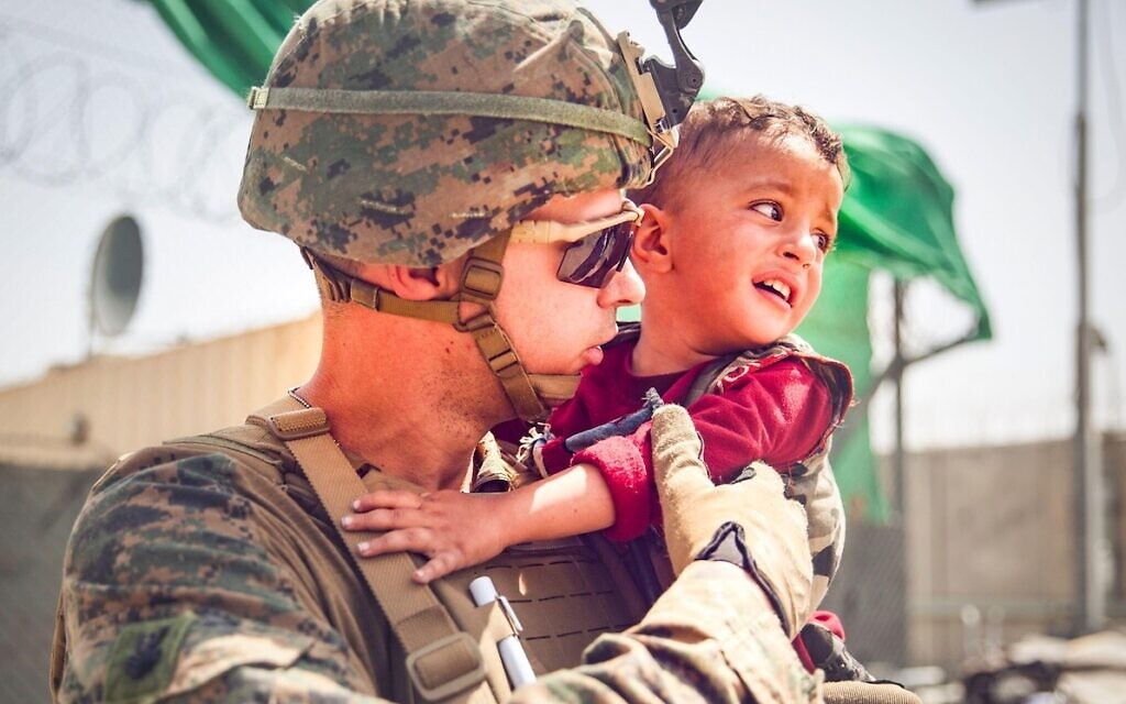 U.S. Marine with the 24th Marine Expeditionary Unit (MEU) calms a crying toddler during an evacuation at Hamid Karzai International Airport, Afghanistan, Aug. 22. U.S. service members are assisting the Department of State with a non-combatant evacuation operation (NEO) in Afghanistan. (U.S. Marine Corps photo by Staff Sgt. Victor Mancilla via American PhotoArchive/Alamy)