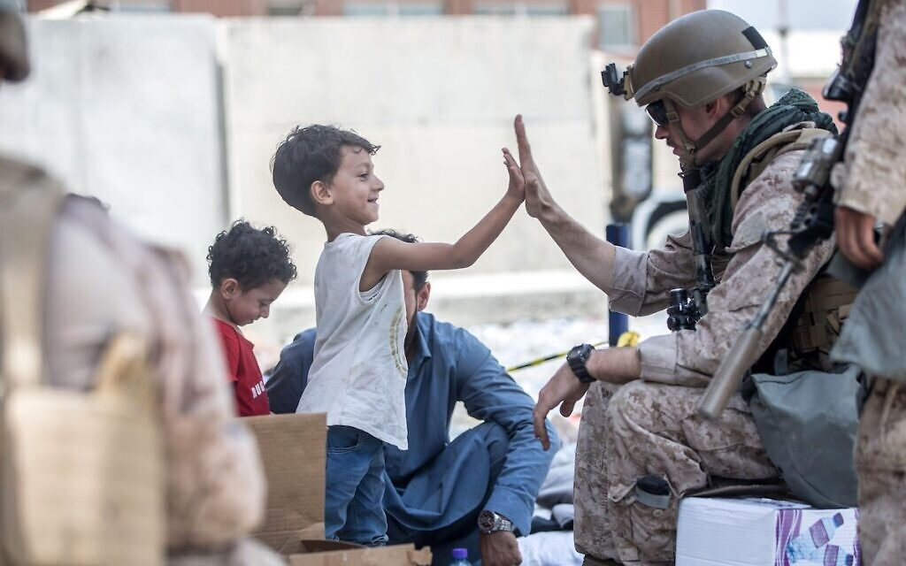 A U.S. Marine with the Special Purpose Marine Air-Ground Task Force-Crisis Response team, high fives a child waiting for evacuation at Hamid Karzai International Airport during Operation Allies Refuge August 22, 2021 in Kabul, Afghanistan.