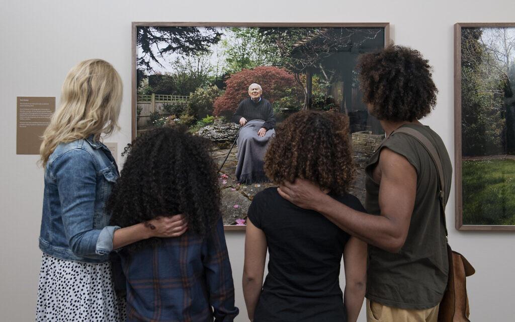 © IWM (0855) Visitors look at Tom Hunter's portrait of Sigi Ciffer, exhibited as part of Generations: Portraits of Holocaust Survivors at IWM London.