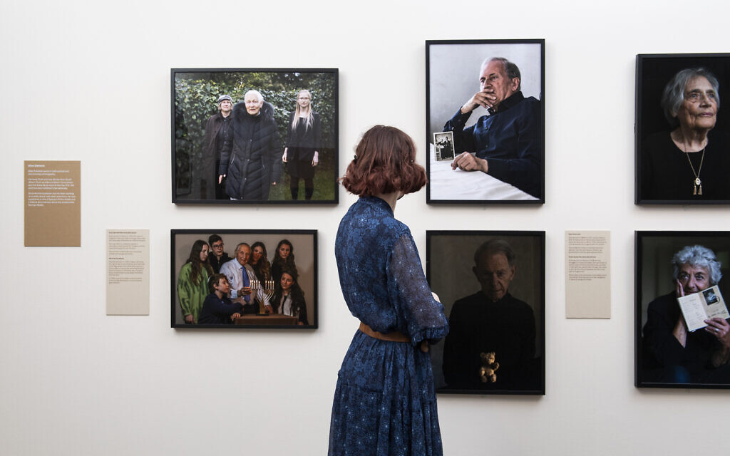© IWM (1048) A visitor looks at portraits taken by Jillian Edelstein for Generations: Portraits of Holocaust Survivors at IWM London.