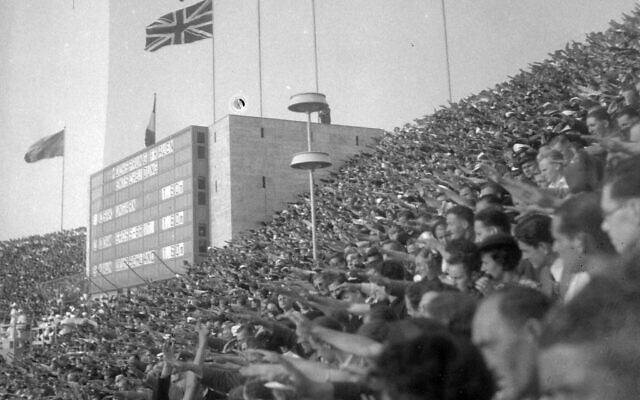 Spectators giving the Nazi salute during one of the medal ceremonies as the Nazi flag flies above (Wikipedia/ FOTO:FORTEPAN / Lőrincze Judit/ CC BY-SA 3.0  / https://creativecommons.org/licenses/by-sa/3.0/legalcode / Sourcehttp://www.fortepan.hu/_photo/download/fortepan_26091.jpg /