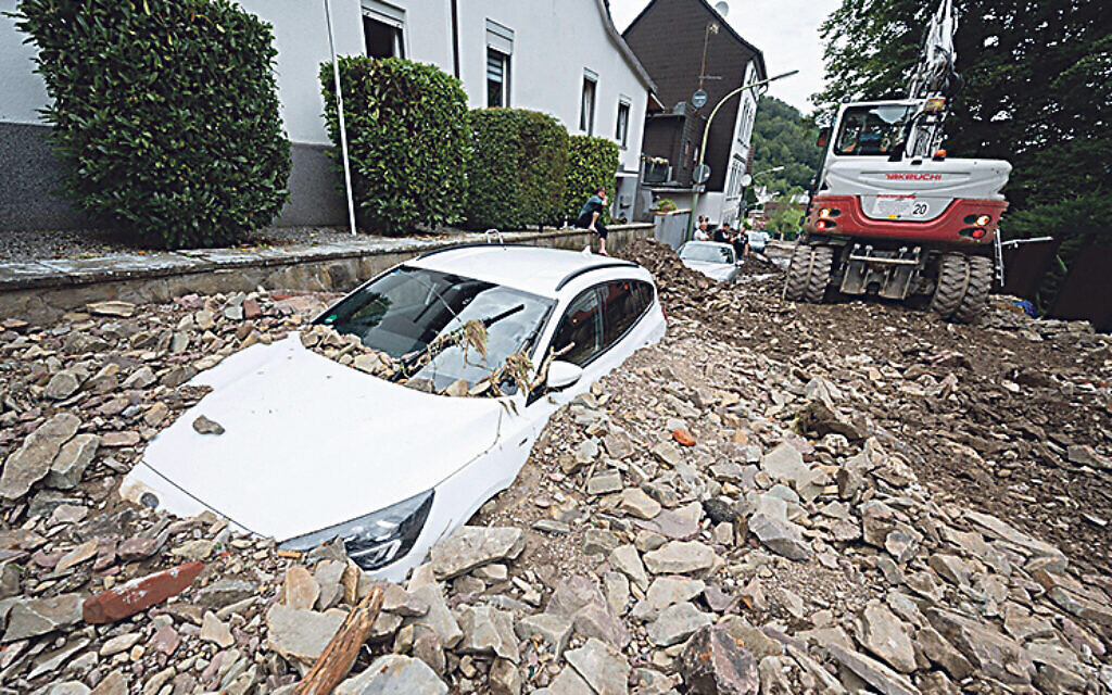 A car is buried by rubble in the Hohenlimburg district. Credit: Julian Stratenschulte/dpa/Alamy Live News