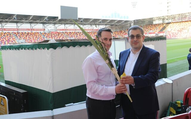 Kevin Coleman (left) shakes a lulav and etrog with Rabbi Goldberg