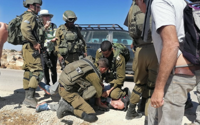 An IDF officer kneels on the neck of activist Tuly Flint in the West Bank on Sept. 17, 2021. (Courtesy of Combatants for Peace)