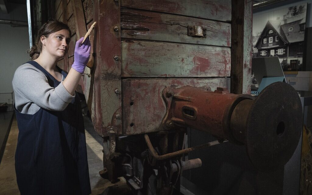 Preservation Technician Emily Thomas cleans a rail wagon of the type used to transport victims to death camps. Pictured in The Holocaust Gallery at IWM London, Lambeth Road. Photographed 30th Sept 2021