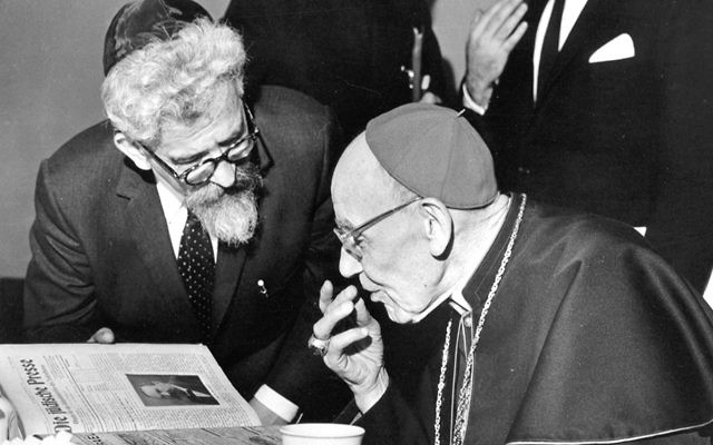 Rabbi Abraham Joshua Heschel and Cardinal Augustin Bea look at a Yiddish newspaper in the offices of the American Jewish Committee in 1963.