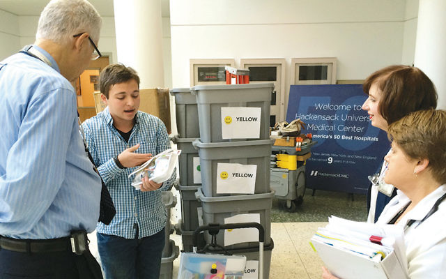 Daniel Nachum, 17, explains his hands-free activity pack to staff members at Joseph M. Sanzari Children's Hospital at Hackensack University Medical Center. The project helped him obtain Eagle Scout rank.