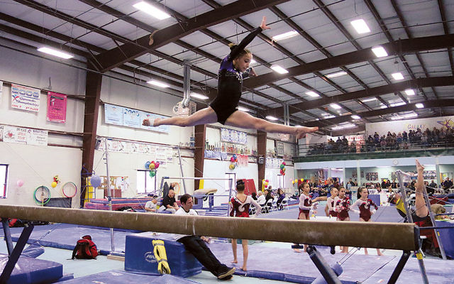 Eden Glick makes a split leap from the balance beam.