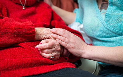 A young hand holding an elderly pair of hands