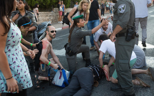 Police and rescue personnel tend to young Israelis wounded in a stabbing attack while participating in the annual pride parade in Jerusalem on July 30, 2015. Six people were stabbed. The suspect in the attack, an ultra-Orthodox man who was protesting against the parade, was arrested. Photo by Miriam Alster/FLASH90