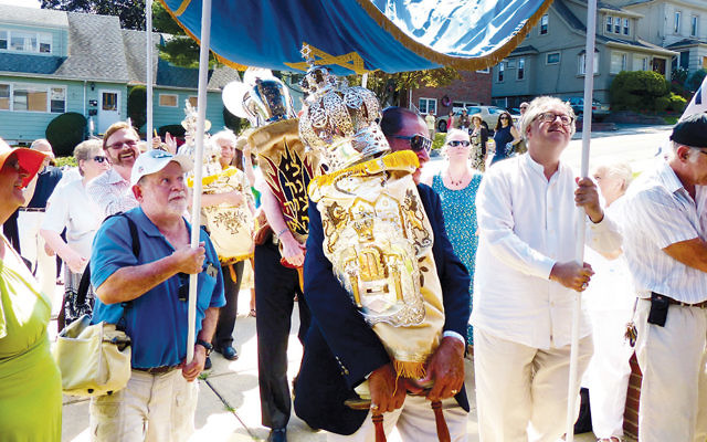 Congregants carry sifrei Torah from their old home to the motorcade that will take them to their new one. (Courtesy of Debbie Beeber)