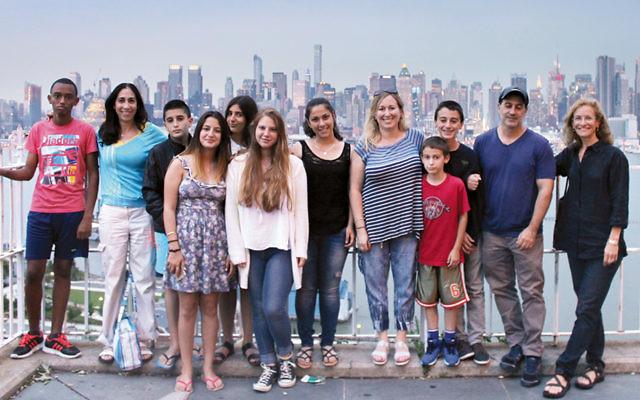 Open Hearts Open Homes kids stand on the Brooklyn Promenade, overlooking Manhattan.