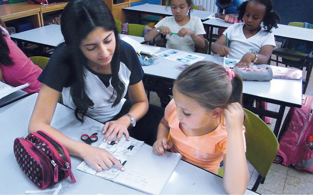 Michelle Bensadigh works with a child in a school in Talpiot.