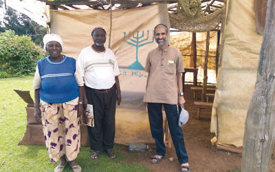 Meylekh Viswanath, at right, with members of the Jewish community in Gathundia, a village in rural Kenya, in front of their makeshift synagogue.